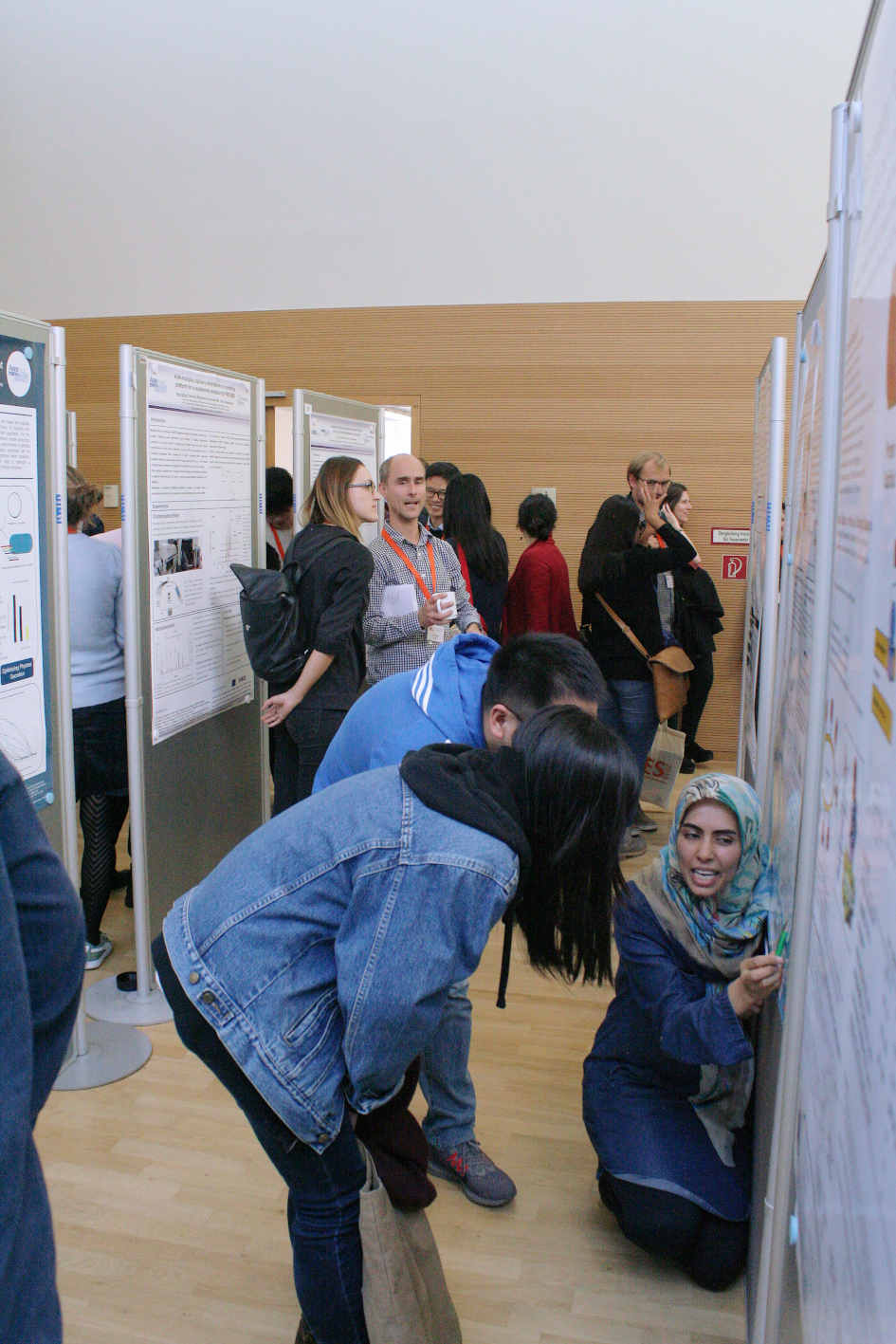 Visitors examine and discuss posters